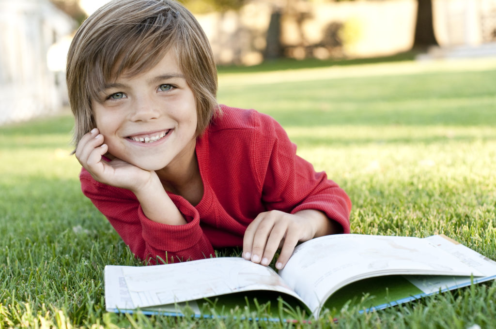 boy lying on the grass reading a kids book